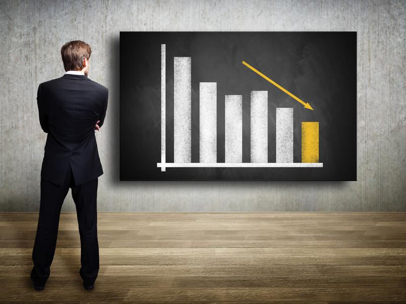 Un homme d'affaire qui regarde un graphique financier où les résultats sont en déclin.