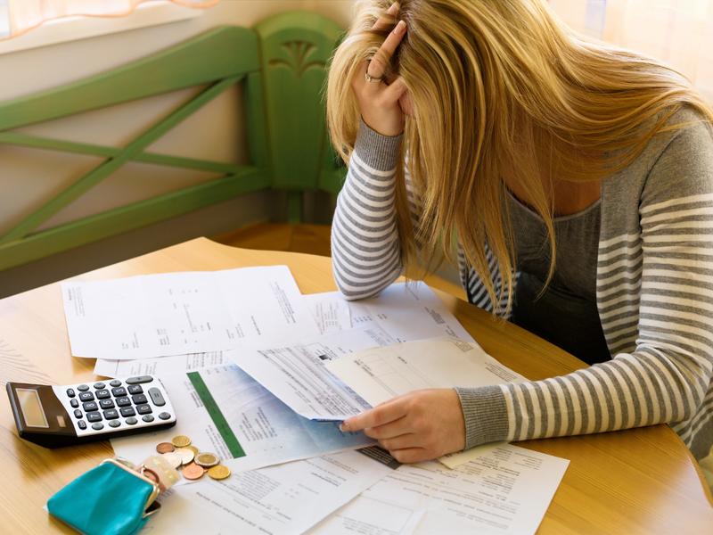 Une femme désespérée qui regarde une feuille. À côté d'elle on voit un portefeuille peu rempli et une calculette.