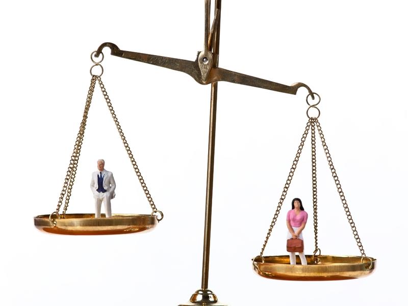 Balance où l'on voit d'un côté un homme et de l'autre une femme. L'homme est plus haut placé que la femme.