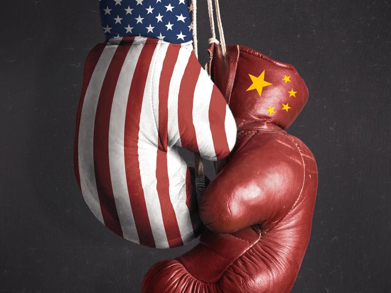 deux gants de boxes accrochés ensemble. L'un d'eux a les couleurs du drapeau américain, l'autre les couleurs du drapeau chinois.