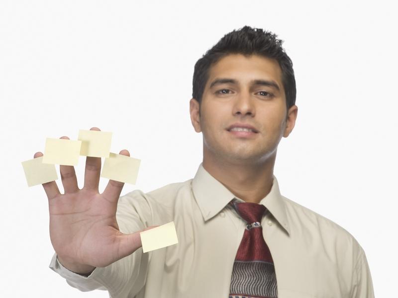 Un homme d'affaire présentant 5 doigts. Sur chacun d'eux, il y a un post it
