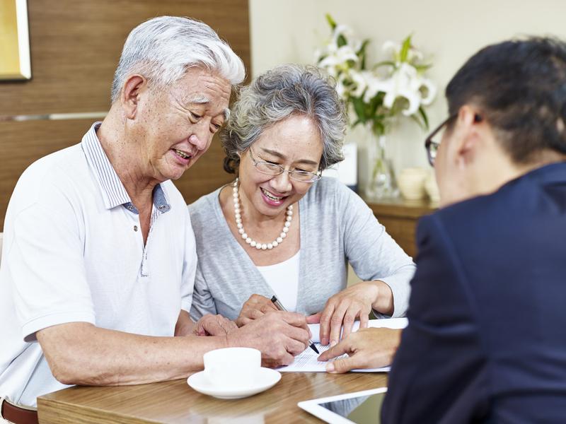 Un couple d'aînés qui sourit en regardant un papier face à un conseiller.