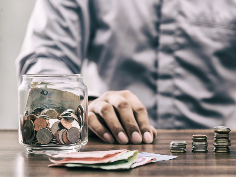 Un homme assis à une table devant un pot plein de monnaie et de la monnaie placée en petits tas devant lui.