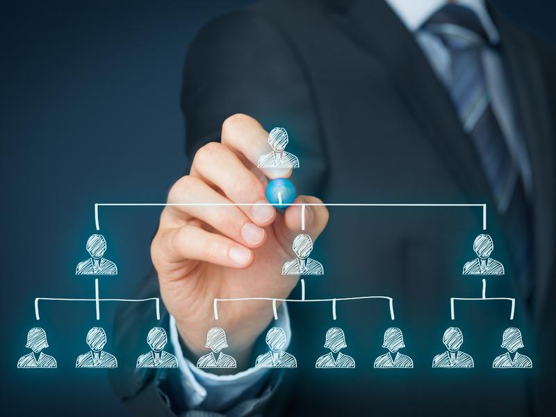 Homme d'affaire plaçant un homme en haut d'un diagramme représentant la hiérarchie.