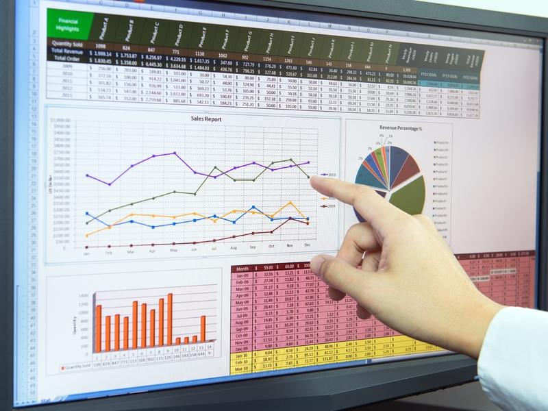 Un homme d'affaire regardant un écran sur lequel on peut lire ses prévisions économiques.