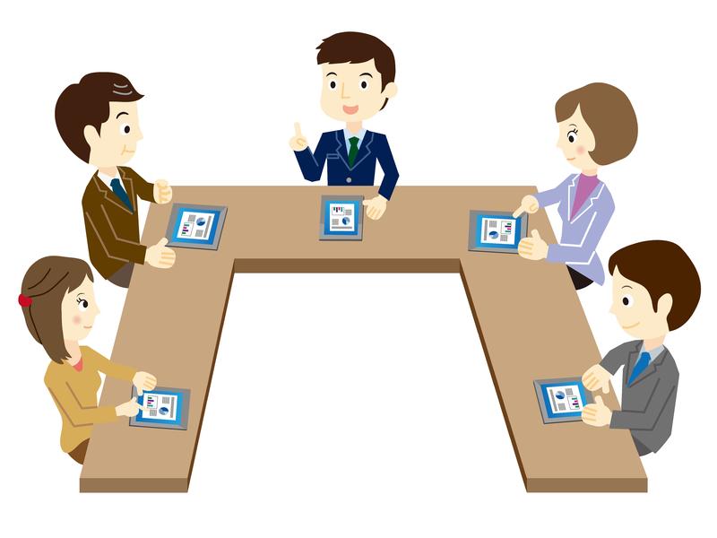 Plusieurs personnes assises autour d'une table en forme de U qui discutent.