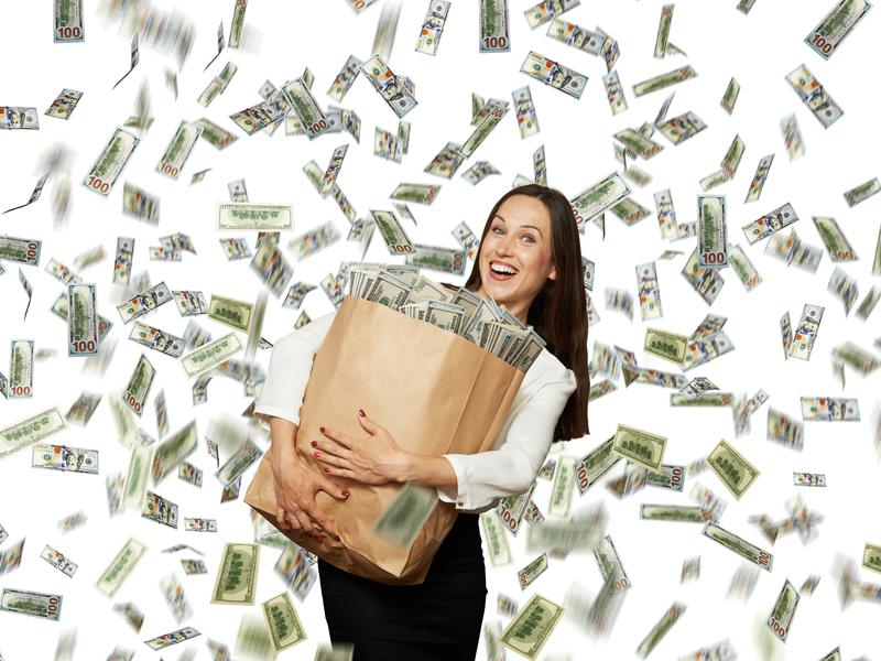 Femme d'affaire tenant un sac de papier rempli d'argent alors qu'il y a une pluie de billets autour d'elle.
