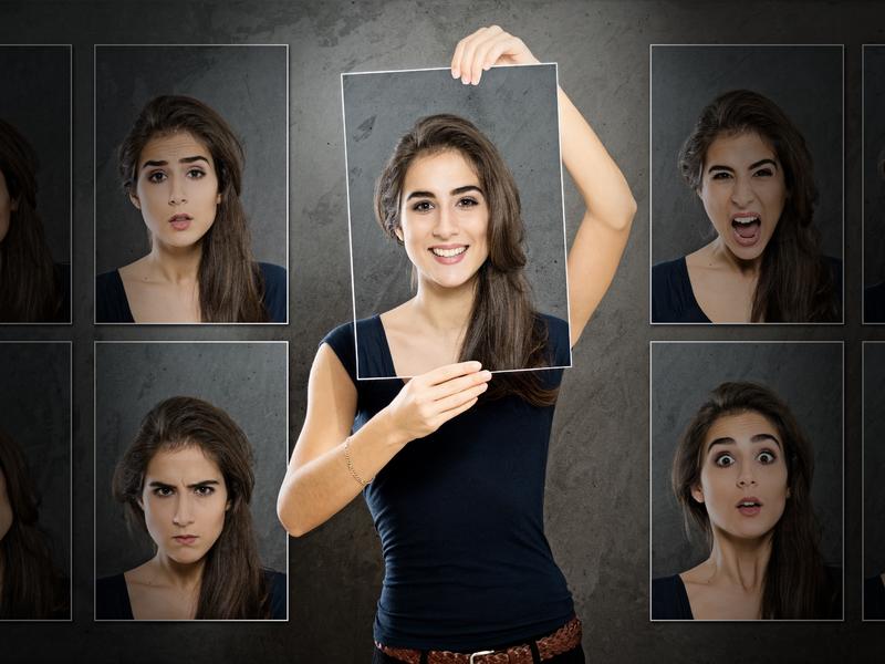 une femme qui tient une photo devant son visage représentant un visage souriant. On voit d'autres photos autour d'elle qui représentent d'autres émotions.