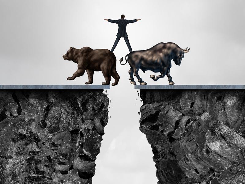 Un homme d'affaire au-dessus d'un gouffre. Son pied droit est posé sur un taureau et le gauche sur un ours.