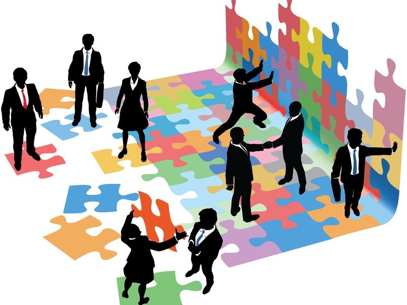 Plusieurs hommes et femmes d'affaires qui font un puzzle colorés.