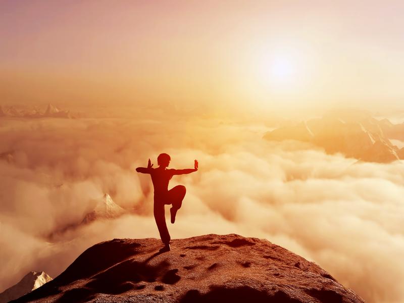 Une personne qui fait de la méditation en haut d'une montagne.