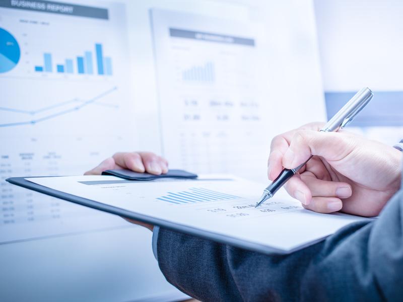 Homme d'affaire tenant une feuille face à un tableau représentant des graphiques financiers.