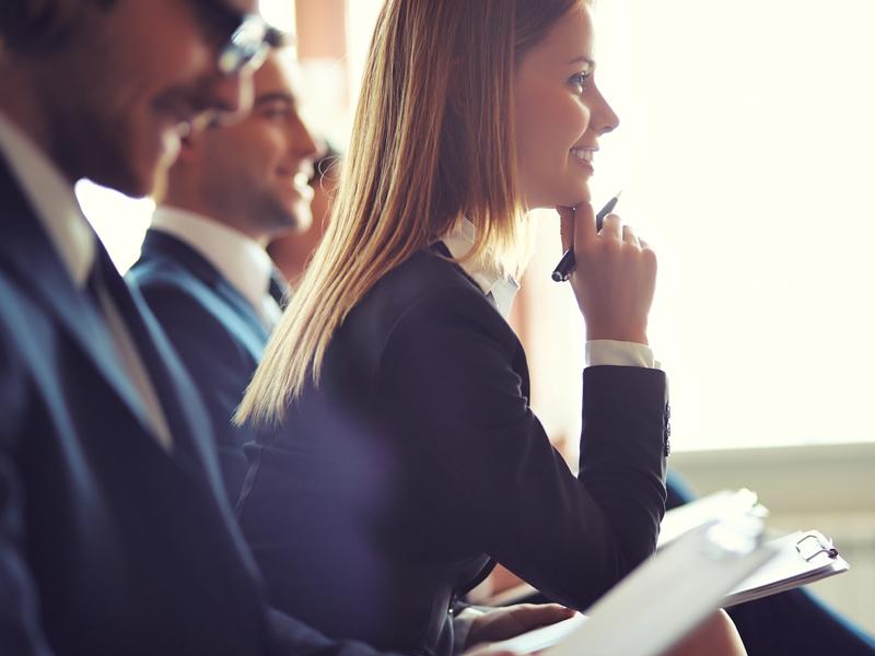 Une femme d'affaire intéressée qui prend des notes entre deux hommes d'affaire.