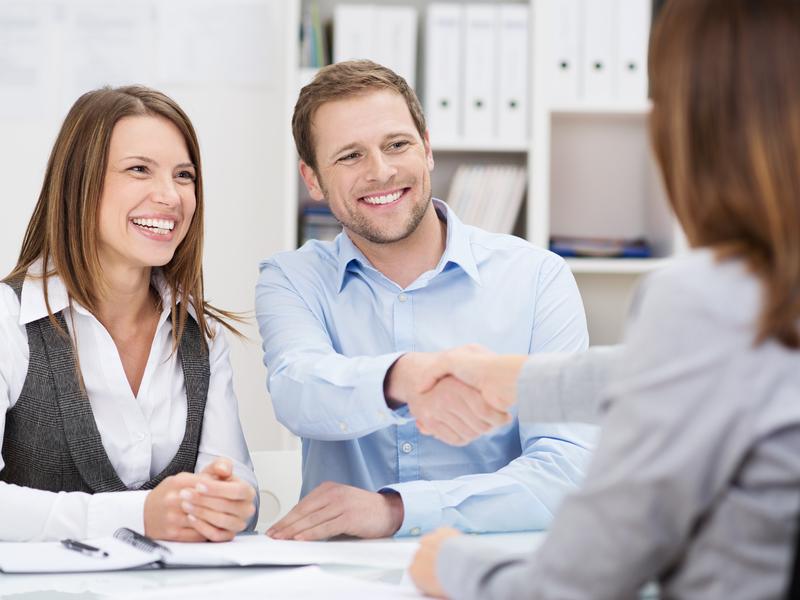 Un couple souriant devant un bureau. L'homme serre la main à une femme en tailleur qui est assise de l'autre côté de la table.