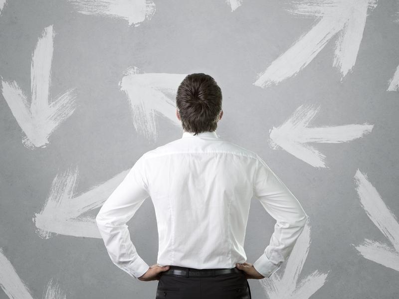 Un homme d'affaires qui contemplent un mur avec des flèches dessinées dessus.