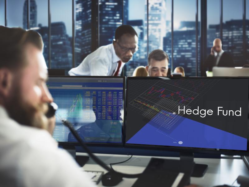 Dans une salle de bourse, un homme est devant un ordinateur sur lequel est inscrit hedge fund. Devant lui on voit deux hommes d'affaire également penchés sur un ordinateur.