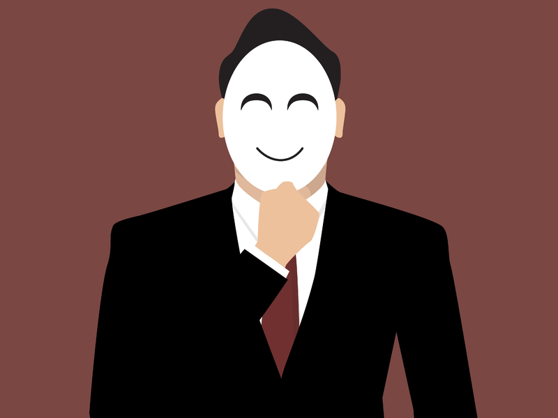 Un homme d'affaire tenant un masque devant son visage pour cacher son identité.