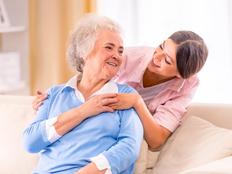 Une femme âgée assise sur un canapé qui regarde sa fille derrière elle qui lui sourit
