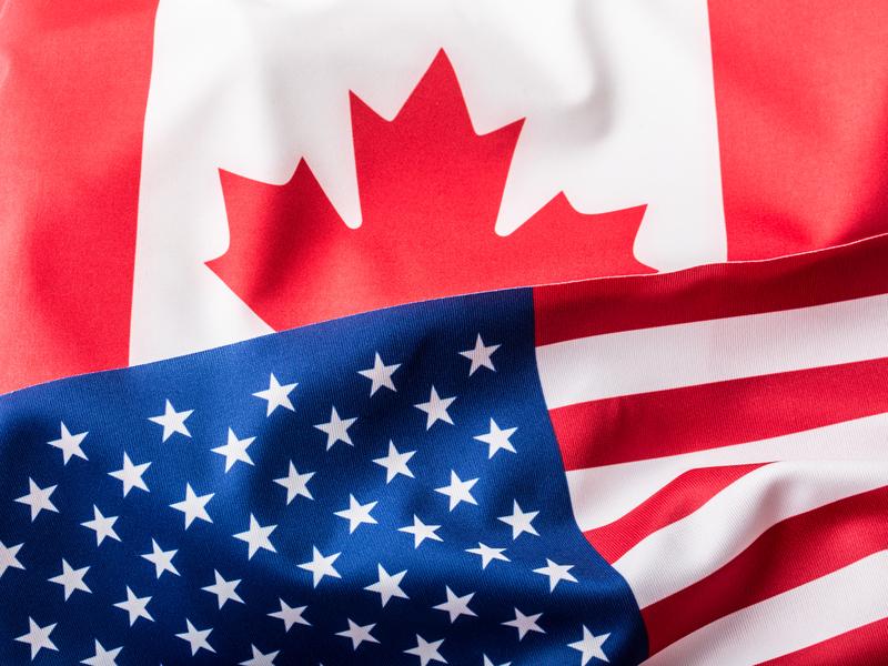 le drapeau américain et le drapeau canadien l'un sur l'autre