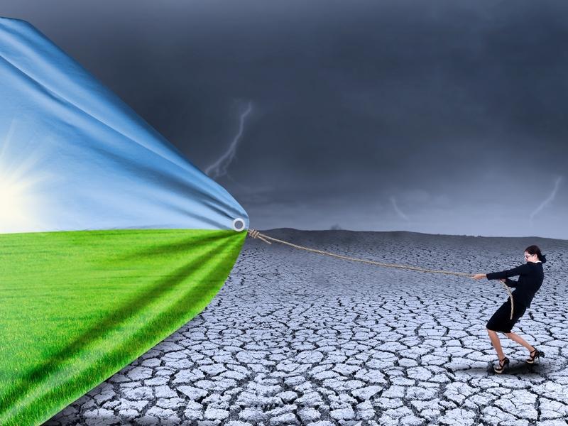 Femme d'affaire dans un paysage désertique qui tire sur une poignée qui amène un paysage ensoleillé.