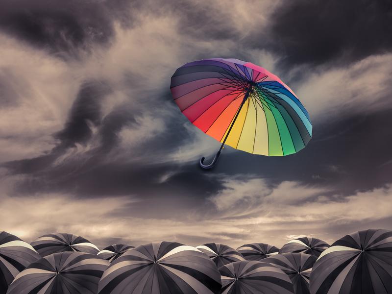 Un parapluie multicolore soufflé loin d'une mer de parapluies noirs.