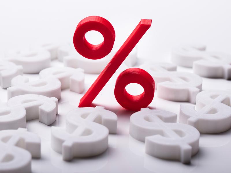 Un signe de taux rouge debout au milieu de nombreux signes de dollars couchés.