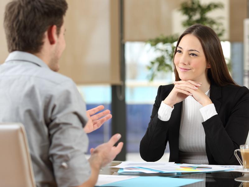 Un homme d'affaire parlant à une autre femme d'affaire qui a l'air très intéressée