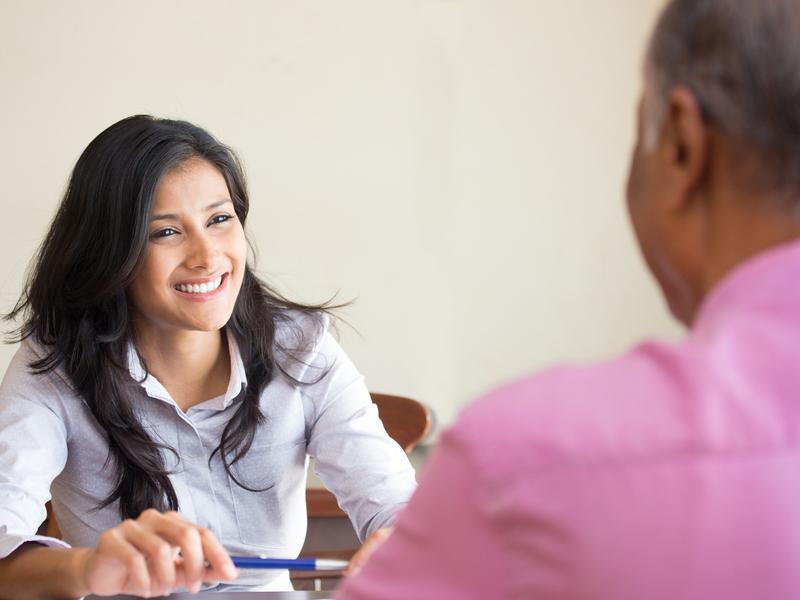 Femme souriante assise à un bureau en face d'un client.