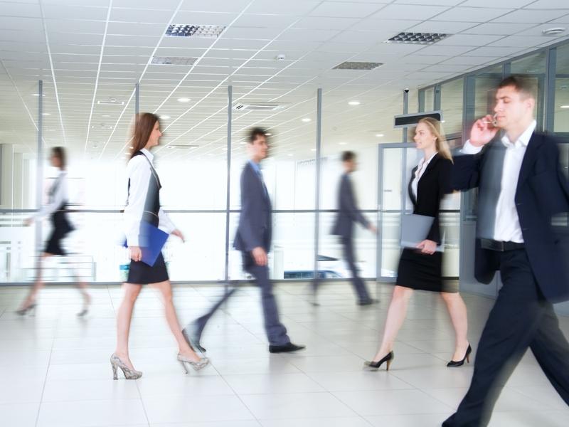 Des hommes et femmes d'affaire marchant dans une pièce.