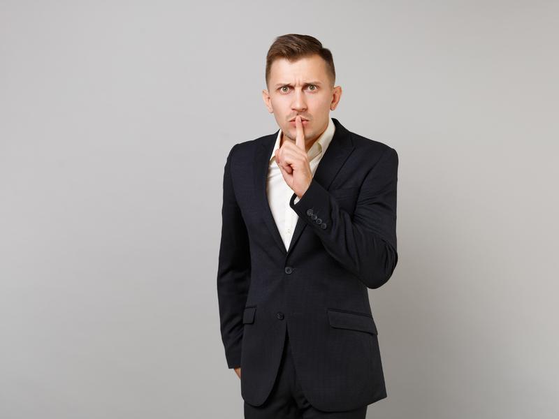 Homme d'affaire avec un doigt sur la bouche demandant le silence.