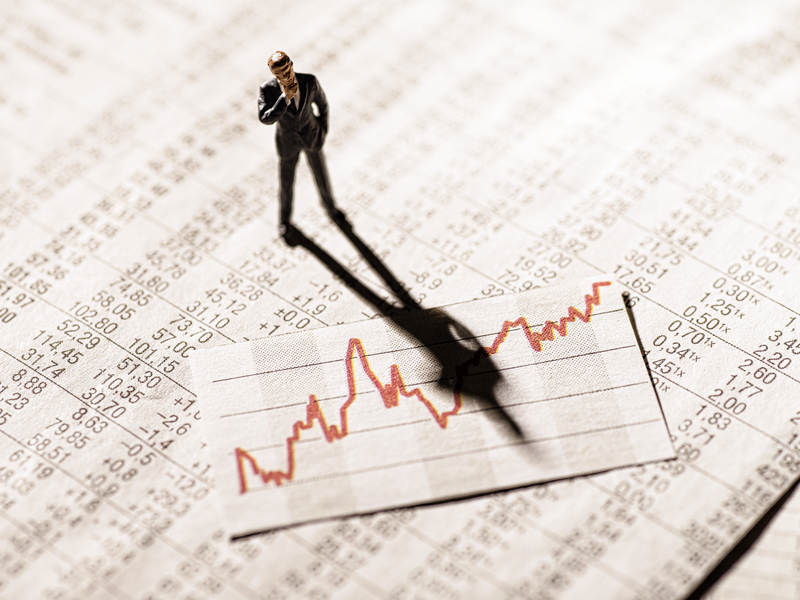 Un petit personnage représentant un homme d'affaire regarde un papier qui représente la volatilité sur des résultats bancaires.