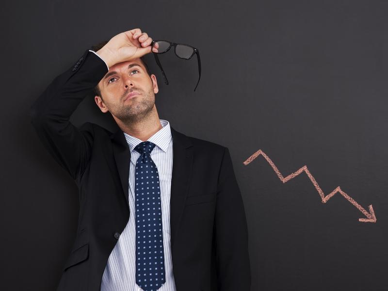 Homme d'affaire déconfit à côté d'une courbe négative.