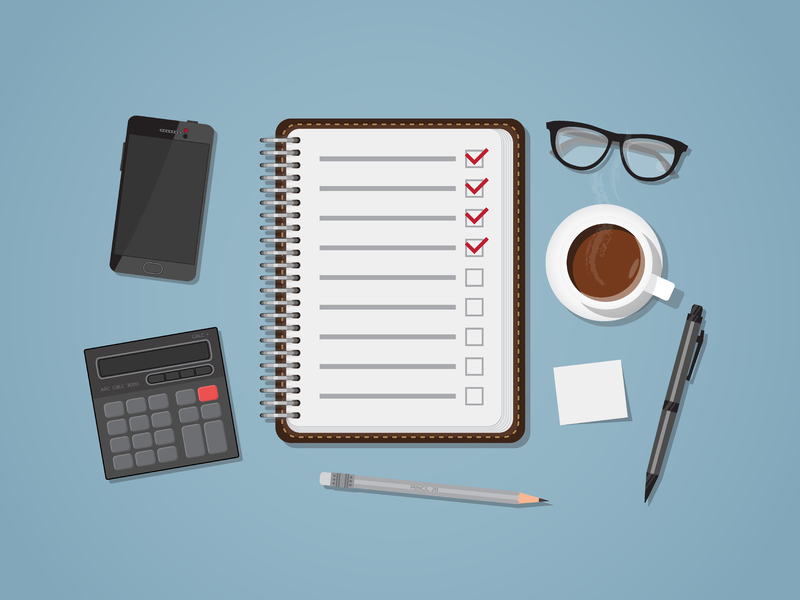 un cahier avec une liste de priorités entouré d'un café, de lunettes, d'une calculette, d'un téléphone et de quoi écrire.