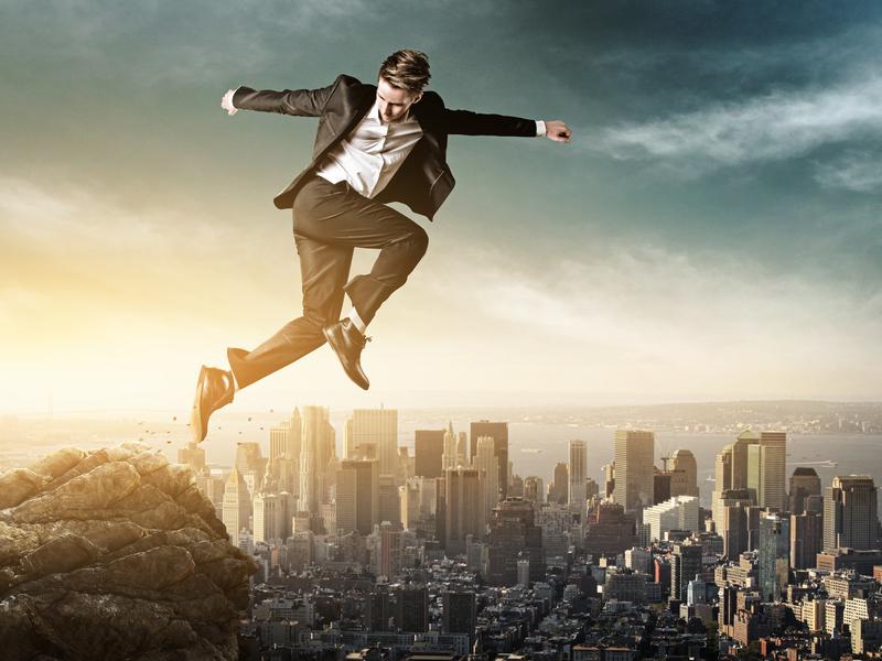 Un homme d'affaire qui saute d'une montagne au-dessus d'une grande ville.