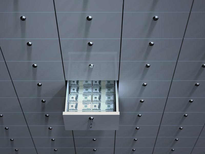Un tiroir parmi pleins d'autres tiroirs identiques. Il est rempli de billets.