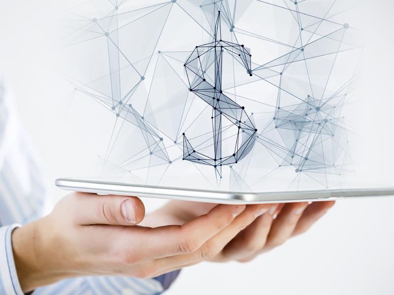 Deux mains tenant un iPad au-dessus duquel se forme un signe de dollar.