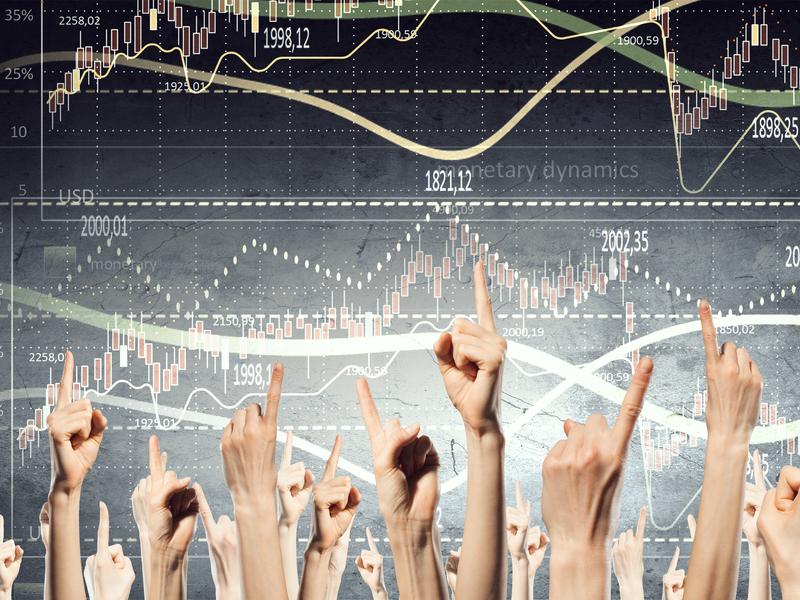 Plusieurs mains avec le doigt levé devant un tableau avec des graphiques financiers