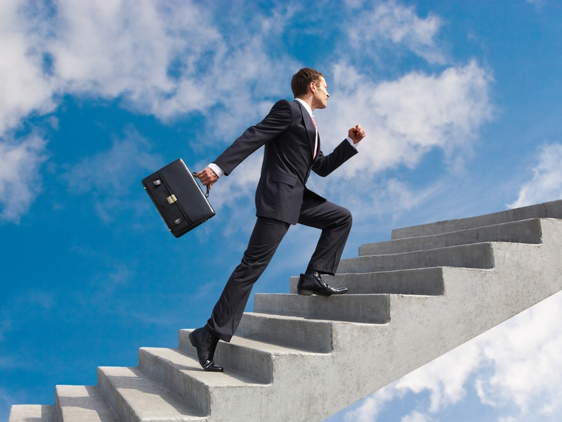 Un homme d'affaire grimpant rapidement des escaliers.
