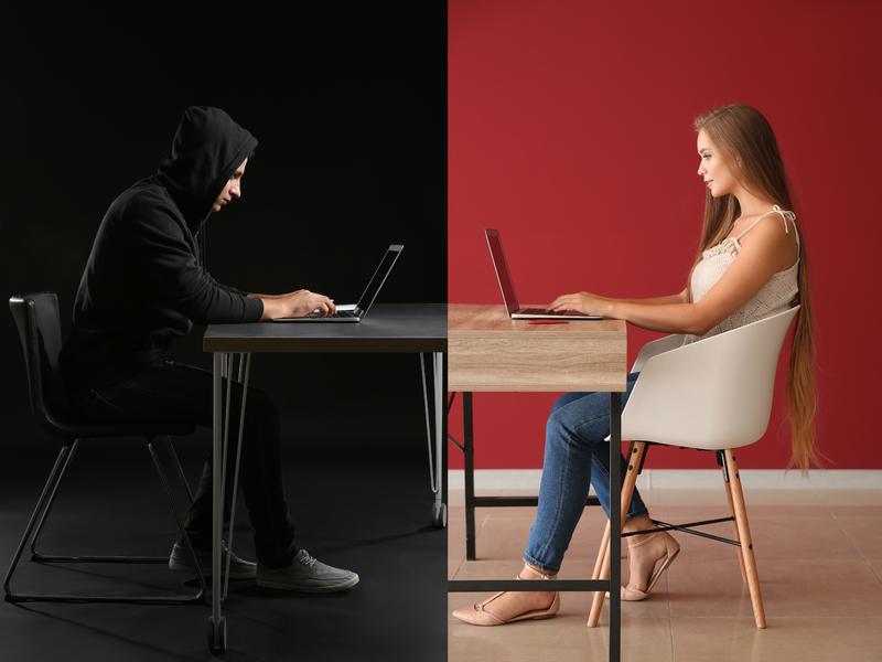 Une femme écrivant sur un clavier à un homme qui a une capuche et a l'air louche.