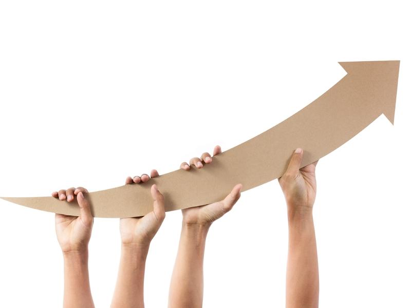 Plusieurs mains tenant une flèche en carton qui fait une courbe vers le haut.