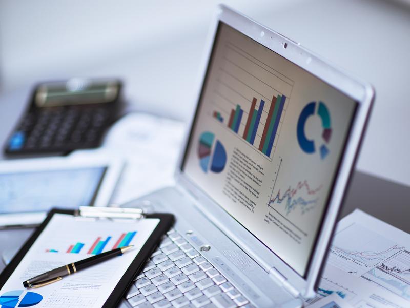 Ordinateur et tablette posés sur une table présentant des graphiques financiers.