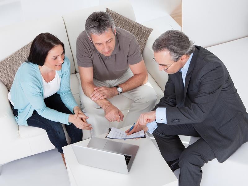 Un homme et une femme assis sur un sofa à côté d'un conseiller financier qui leur montre un papier.