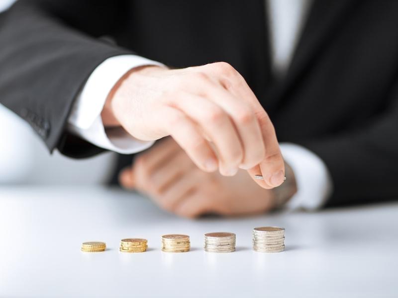 Un homme d'affaire faisant des petites piles de pièces de monnaies.