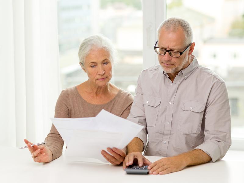 Couple d'aîné avec une calculette en regardant un feuille l'air soucieux.