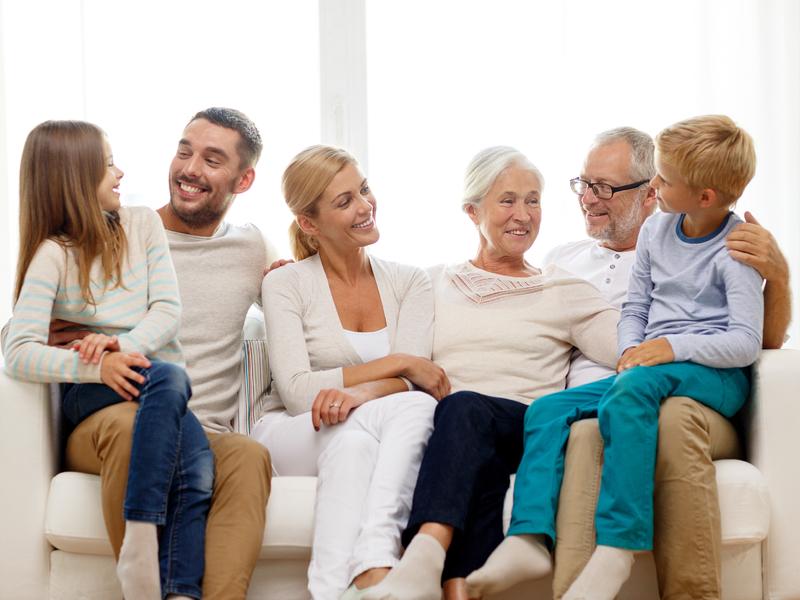 Une famille multigénérationnelle assise sur un canapé blanc.