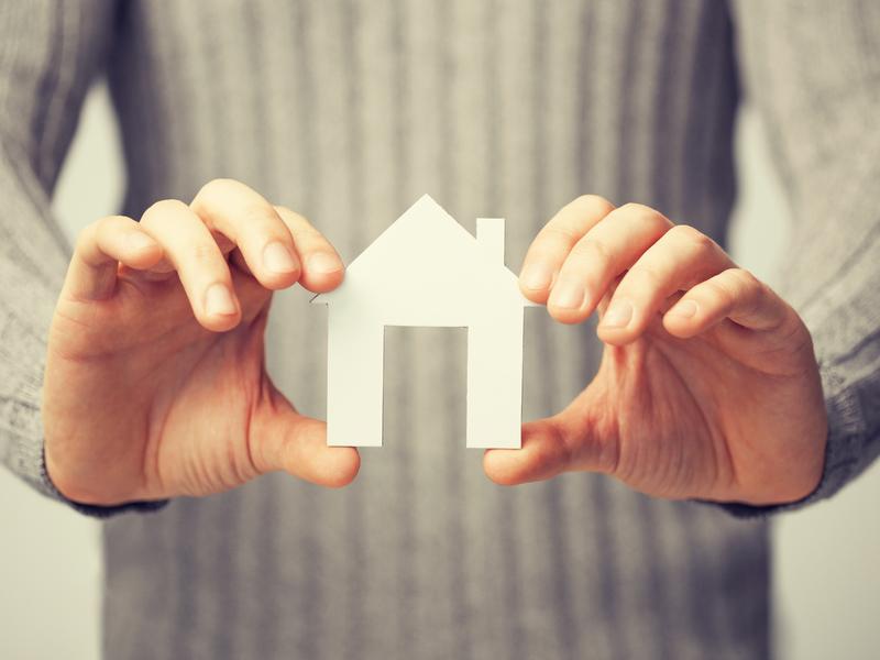 Une femme tenant une maison en papier entre ses mains.