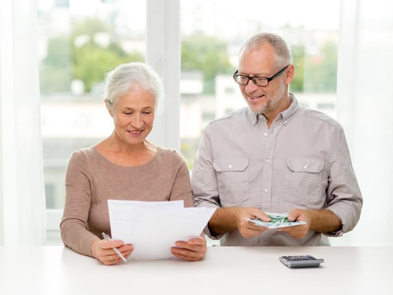 Un couple d'aînés qui regardent leurs papiers financiers avec l'air heureux.