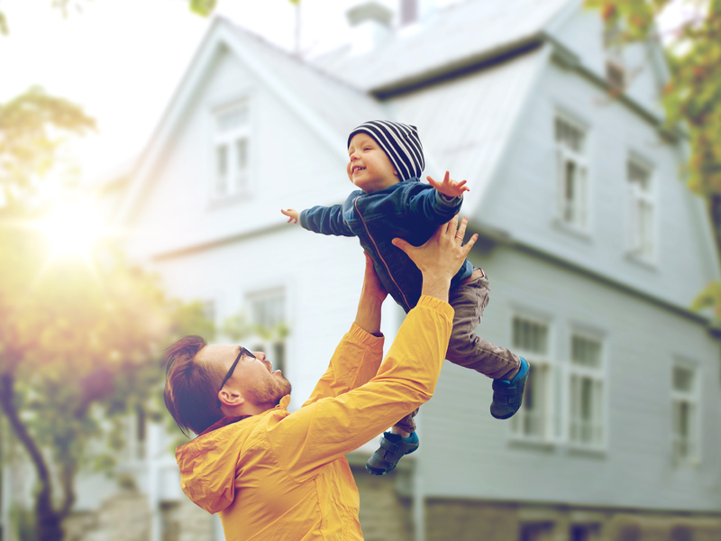 Un père qui tient son enfant à bout de bras devant une maison.