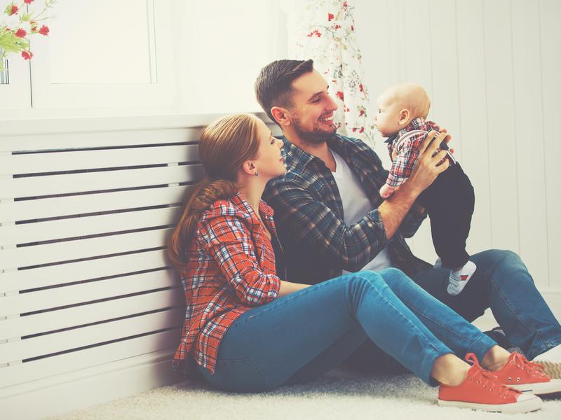 Un père et une mère assis sur le sol côte à côte. Le père tient un bébé dans ses bras.