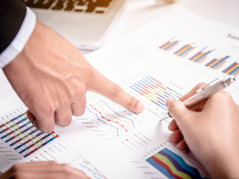 Deux personnes qui analysent des graphiques financiers.